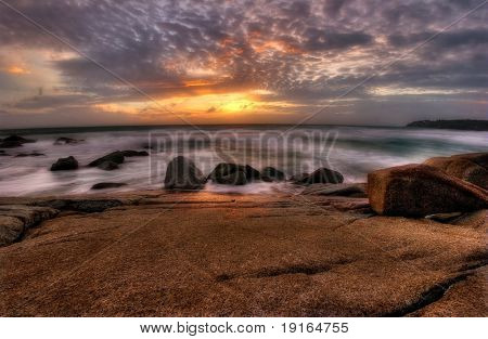 Great sunset on the rocks near tropical beach. Andaman sea. Phuket island. Kingdom Thailand poster