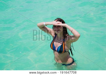 Happy woman in swimsuit stands in water of the ocean coast during holidays summer time.