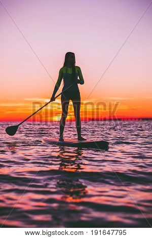 Girl stand up paddle boarding on a quiet sea with warm sunset colors