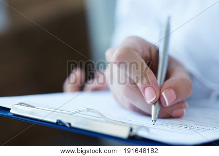 Close-up view of female doctor's hands filling patient registration or prescription form. Healthcare medical and pharmacy concept.