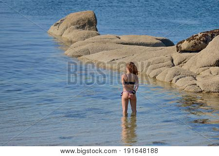 young woman in a bathing suit standing in the water, rear view