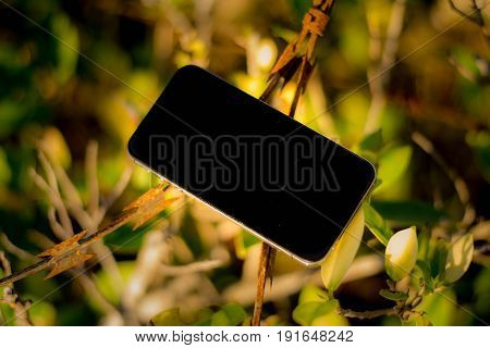 Mobile phone on old barbed wire and bright backgroup