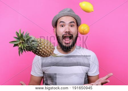 Men are throwing oranges lemons and pineapple flavors on a pink background.