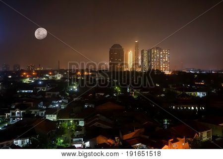 City panorama with building in night skyline with moon and lights extending to the horizon