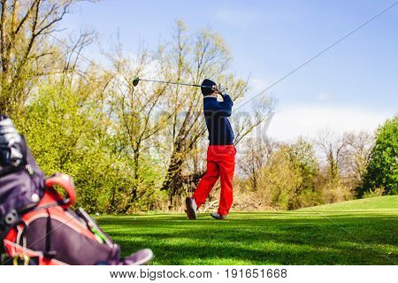 golfplayer hits a ball on the grass