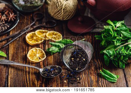 Dry Tea in Strainer and Spoonful of Tea with Fresh Mint Lemon Slices. Tangle with Two Jars and Teapot on Backdrop.