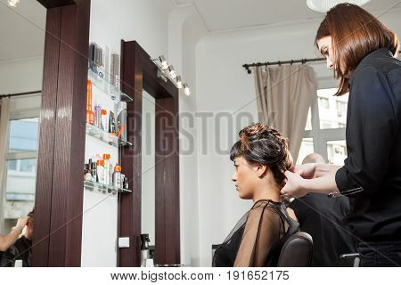 Gorgeous woman at the hair salon getting a new hairstyle. Professional service. New hairstyle. Stylist at work