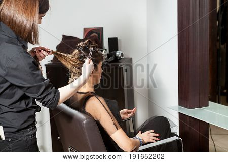 Woman getting hair treatment at the hair salon. Professional service. New hairstyle. Stylist at work