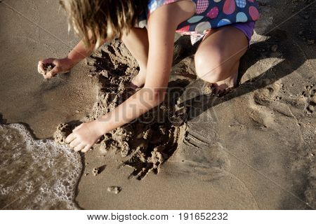 Little girl playing sand by the seashore