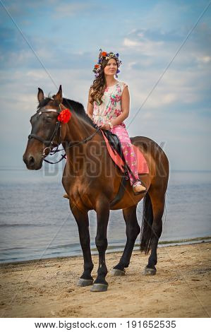 Beautiful woman on a horse by the sea. Sunset by the sea.