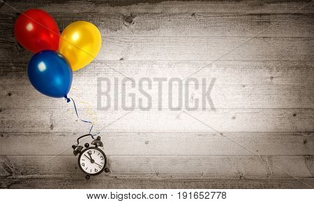 Time fly -Clock flying with several balloons on a wooden background