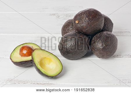 One sliced and several whole avocados on a white painted wood background.
