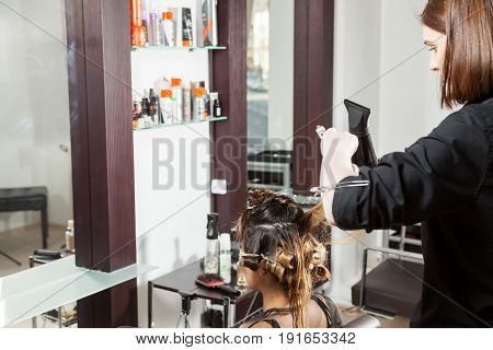 Gorgeous woman at the hair salon getting a hairstyle. Professional service. New hairstyle. Stylist at work