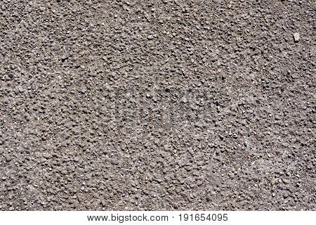 Grey concrete floor surface with rough gravel