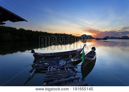 longtail boat with coastal fishing village Beautiful morning sunrise over sea and mountain in phang - nga thailand.