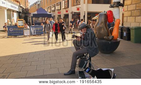 CAMBRIDGE UK-APRIL 10: many tourists enjoy nice weather outside in market hill with the song played by street music in Cambridge university the second-oldest university in the english-speaking world in summer on April 10 2017