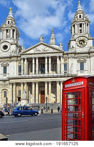 LONDON, ENGLAND - May 25,2017: famous red telephone booth on the background of the western facade of St. Paul Cathedral in London, UK