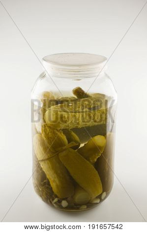 in a glass jar plenty of green cucumbers in marinade