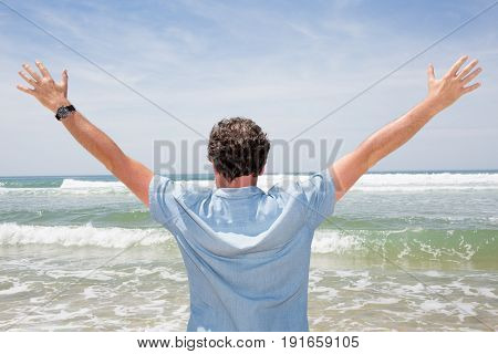 Handsome Man Facing The Ocean With His Arms In The Air