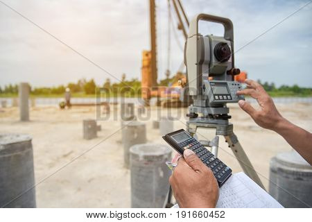 Close up hand civil engineer Using calculator Surveyor equipment tachometer or theodolite outdoors at construction road or construction site foundation structure work