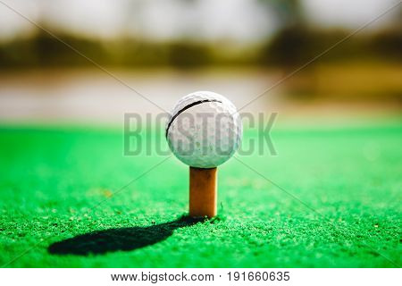 golf ball on green tee close up