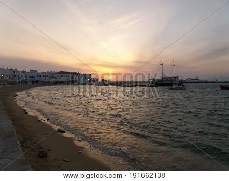 Impressive sunset in Mykonos town with many boats at the Old Port, Mykonos Island, Greece