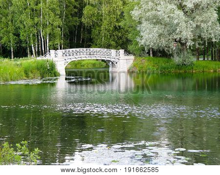 white stone bridge across the river on a background of green trees