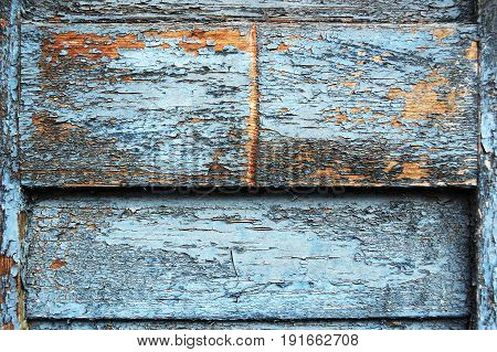 A fragment of a wall paneled with threadbare scratched wooden boards