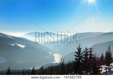Misty winter day in the mountains with rays of light