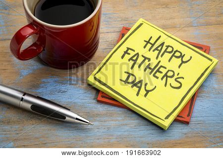happy father's day - handwriting in black ink on a sticky note with a cup of coffee