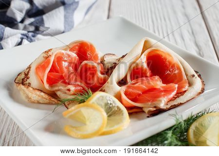 Luxury pancakes with red fish on white plate. Russian traditional salty crepes with seafood. Shrove tuesday holiday food