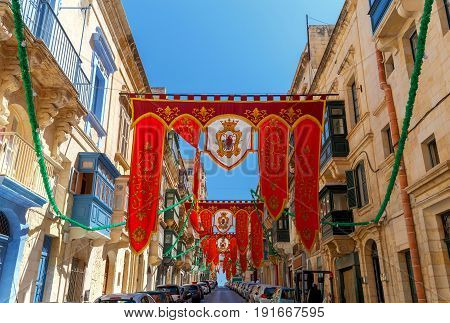 Festively decorated street with flags for the feast of St. Augustine in old town. Malta. Valletta.