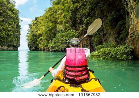 Woman on kayak in calm tropical lagoon on Koh Hong island