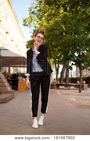Fashionable women's look with black jacket, blue blouse and white sneakers. Fashion concept