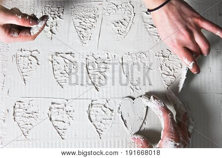 Creative art, hand make heart stamps on white plaster, flat lay. Stucco texture, decorative design, handmade pattern , love concept.