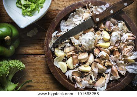 Cloves garlic on a wooden plate