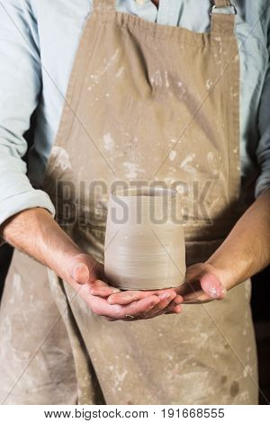 pottery, stoneware, ceramics art concept - young man in a dirty apron stand at workshop, master hands holds cup of unfired clay, male examines product before further processing, front view, vertical