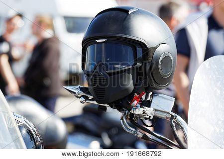 Black Moto Helmet On Motorcycle Handlebars