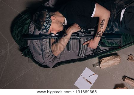 Gangster sleep with rifle. Gang wars concept. Cigarette, alcohol, weapon top view. Careless lifestyle, social problem, negative addiction concept