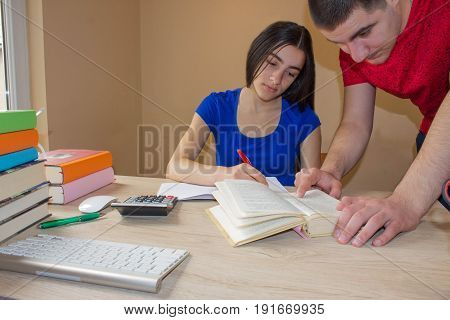 Older brother Helping Student sister Working At Desk with writing lesson