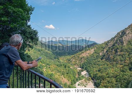Thueyts, France, september 11, 2016: Man with newspaper in hands enjoys the view over the valley where the river Ardeche flows