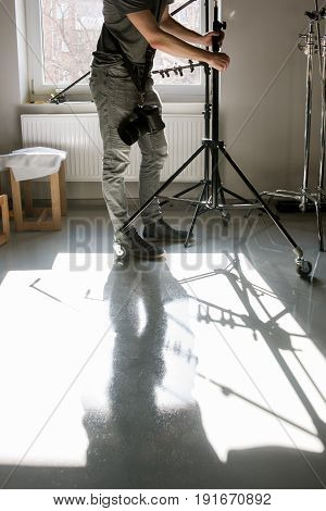 Unrecognizable man setting the photo tripod. Assistant work with equipment in photostudio. Professional photographer is adjusting studio for photographing.