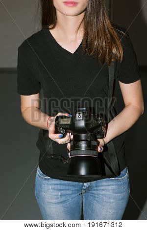 Female photographer and black camera. Unrecognizable young woman photographing something with professional equipment in studio