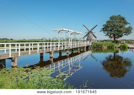 White drawbridge over the canal to reach one of the mills at the Kinderdijk in The Netherlands.