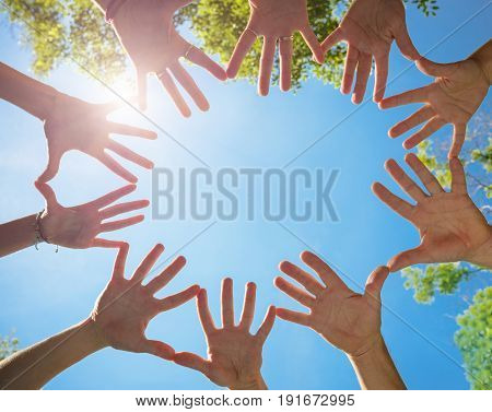 people hands together on blue sky background