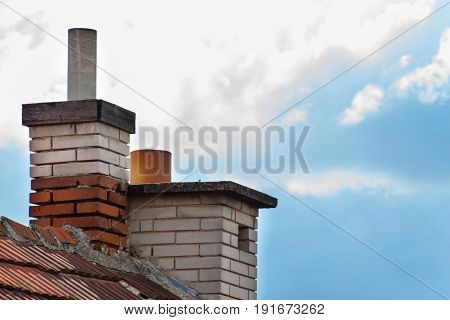 Old brick chimney on the roof. Air pollution