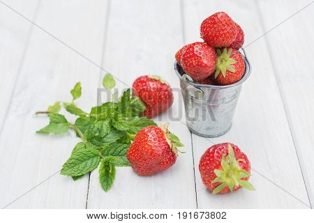 Small metal bucket filled with strawberries and a sprig of mint.
