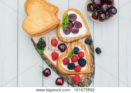 Bowl filled with cherries and heart shaped biscuits spread with quark cherries and a twig of mint presented on a tree disk