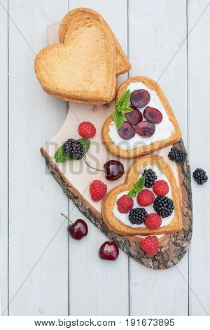 Heart shaped biscuits spread with quark cherries and a twig of mint presented on a tree disk