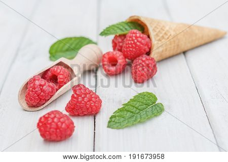 Cones and spoon with raspberries and a twig mint spread over a white table top